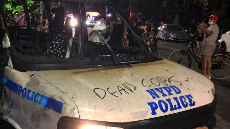 The remains of a scorched police vehicle lie vandalized during riots in the Fort Greene neighborhood in the Brooklyn borough of New York on May 29, 2020. - The woman who threw the molotov cocktail inside the vehicle occupied by four officers on the fringes of a demonstration in New York on Friday was arrested