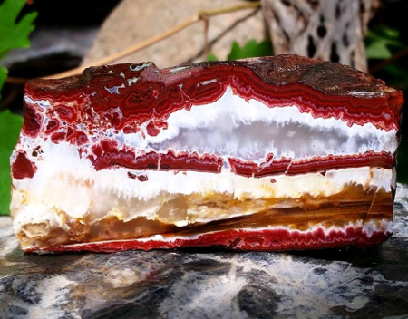 Lies!  The cake is a lie! It's a rock, specifically a striation of red agate, white opal, and botryodial chalcedony